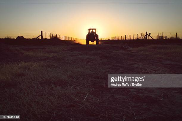 silhouette tractor at farm field against clear sky during sunset - andres ruffo fotografías e imágenes de stock
