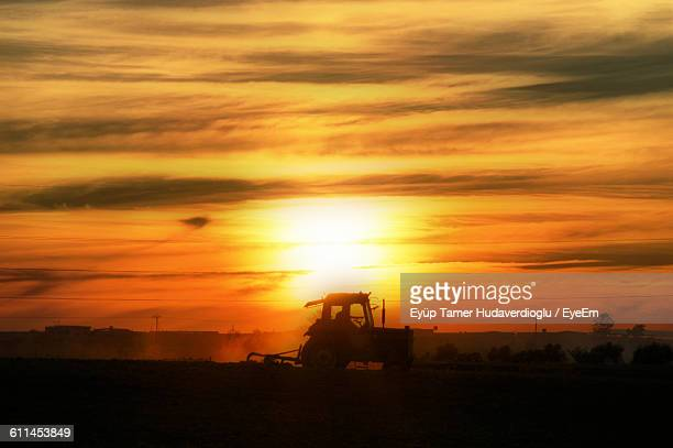 Silhouette Tractor On Field Against Sky During Sunset
