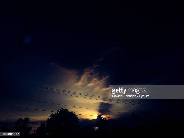 silhouette trees and power cables against dramatic sky at dusk - johnson stockfoto's en -beelden