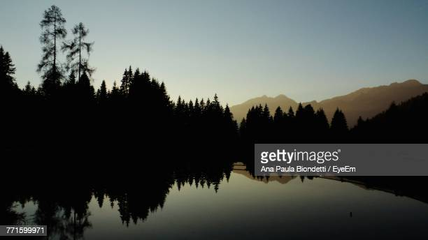 Silhouette Trees By Lake Against Sky During Sunset