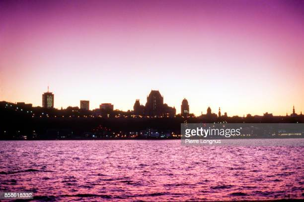 silhouette view at dusk of the historic district of quebec city from the other side of the the st. lawrence river, quebec, canada - hot pink stock pictures, royalty-free photos & images