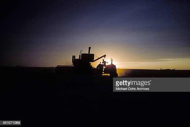 Silhouette view of a farmer on tractor and combine harvester in Oakley, Kansas.