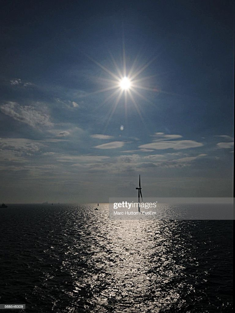 Silhouette Wind Turbine In Sea Against Sky During Sunny Day : Stock Photo