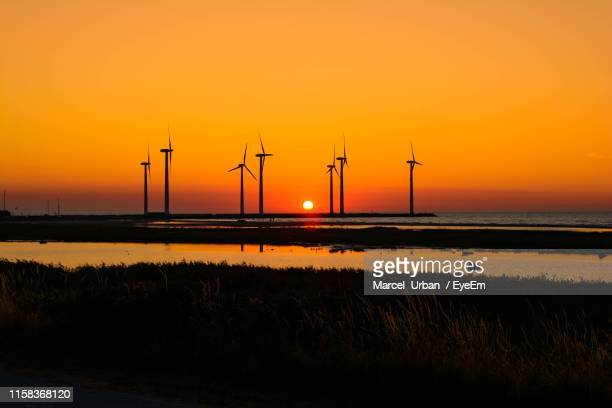 silhouette wind turbines on field against sky during sunset - denmark stock pictures, royalty-free photos & images