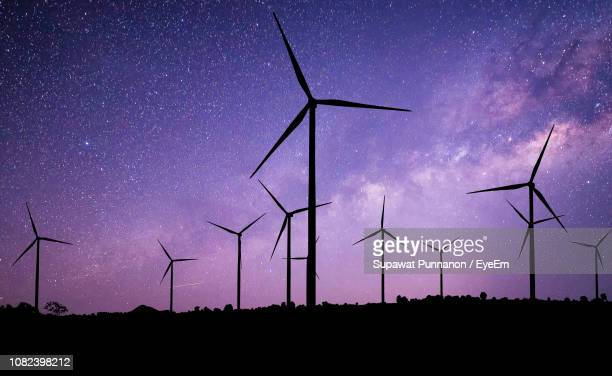 silhouette windmills against star field at night - wind power stock pictures, royalty-free photos & images