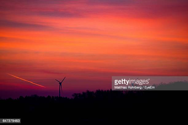 silhouette windmills on field against orange sky - american style windmill stock pictures, royalty-free photos & images