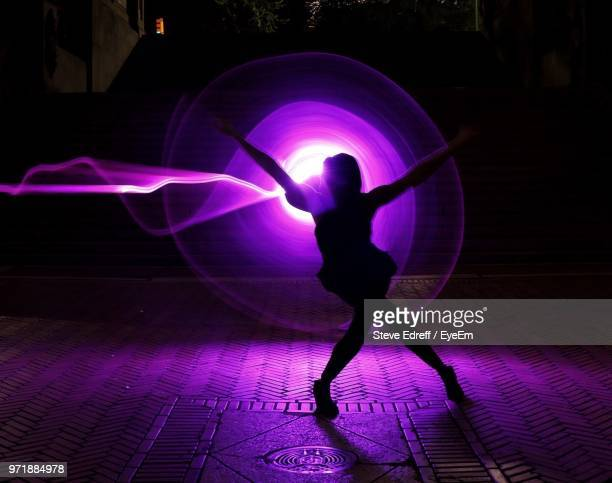 silhouette woman against purple light painting on street at night - lichtmalerei stock-fotos und bilder