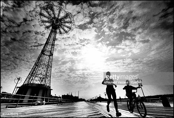 silhouette woman and boy by parachute jump against sky in city at coney island - ブルックリン コニー・アイランド ストックフォトと画像