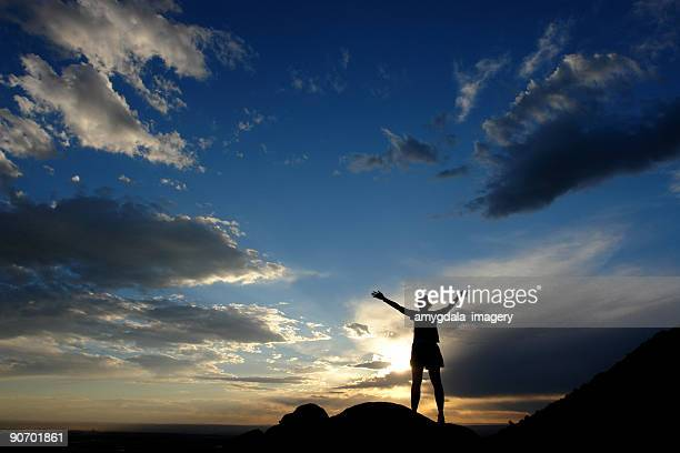 silhouette woman arms raised into sunset sky landscape