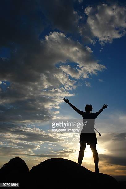 silhouette Frau Arme hoch in den Himmel bei Sonnenuntergang