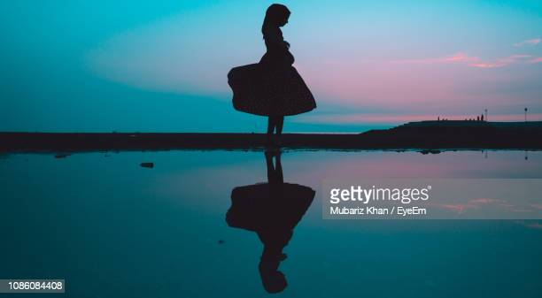 silhouette woman at beach against sky at night - kagawa ストックフォトと画像