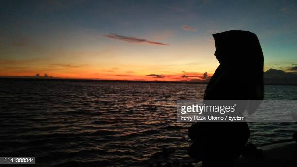 silhouette woman at beach against sky during sunset - muslim woman beach stock photos and pictures