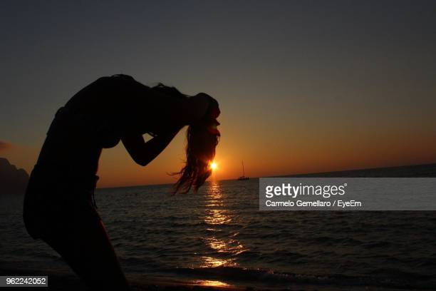 silhouette woman bending by sea against sky during sunset - carmelo ストックフォトと画像