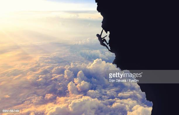 Silhouette Woman Climbing Cliff Over Cloudscape During Sunset