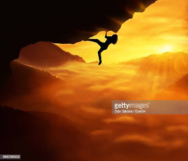 Silhouette Woman Climbing Rock Against Orange Sky