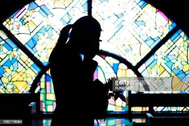 silhouette woman crying against stained glass - 安らかに眠れ ストックフォトと画像