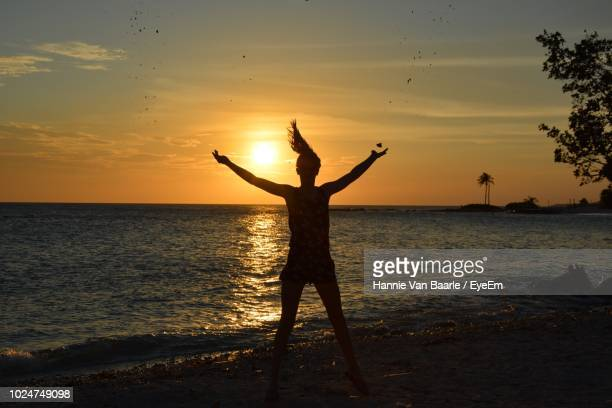 Silhouette Woman Dancing At Beach Against Sky During Sunset