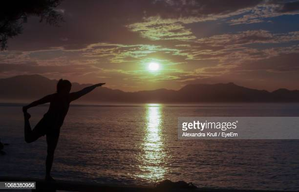 Silhouette Woman Doing Yoga At Beach Against Sky During Sunset