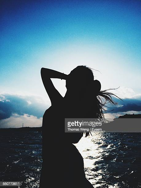 Silhouette Woman Enjoying Wind At Lakeshore Against Blue Sky