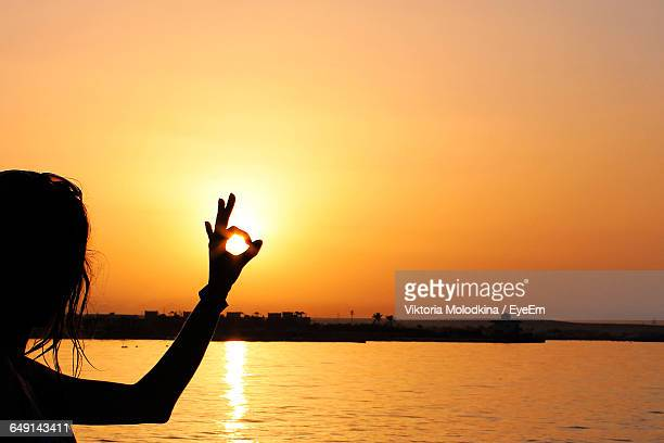 Silhouette Woman Gesturing By Sea Against Sky During Sunset