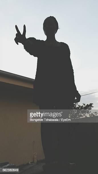 Silhouette Woman Gesturing Peace Sign By Wall Against Sky