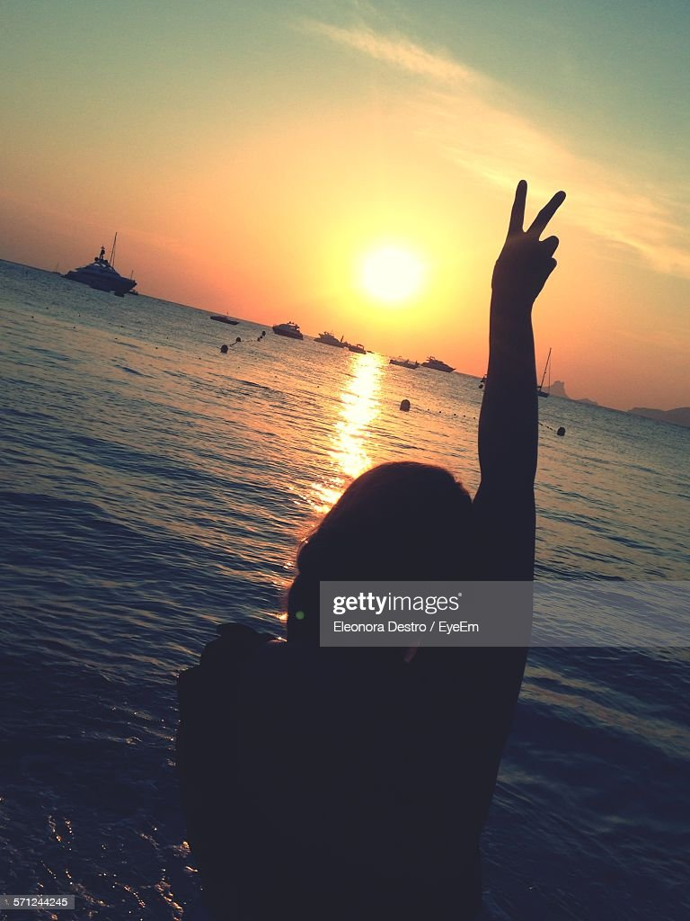 Silhouette Woman Gesturing Peace Sign On Beach Against Sky During Sunset : Stock Photo