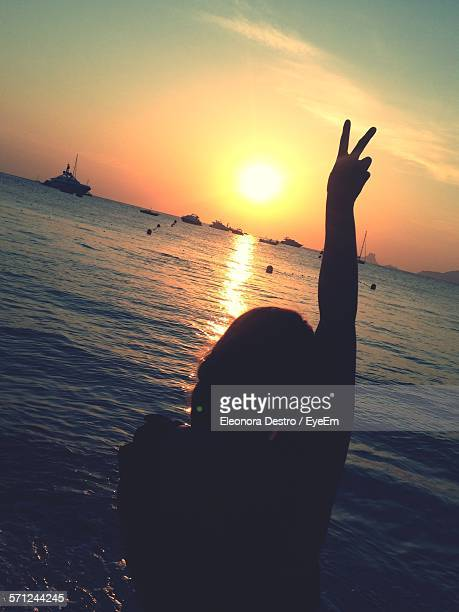Silhouette Woman Gesturing Peace Sign On Beach Against Sky During Sunset