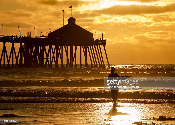 Silhouette Woman Holding Surfboard On Shore Against Cloudy Sky During Sunset