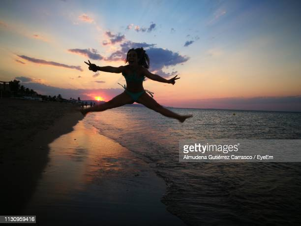 Silhouette Woman Jumping Against Sea During Sunset