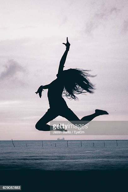 Silhouette Woman Jumping At Beach Against Sky
