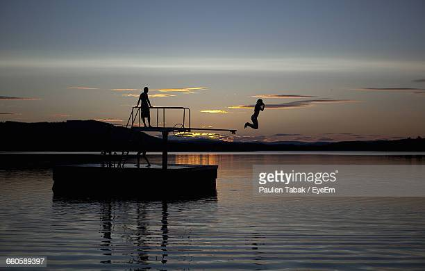 silhouette woman jumping in lake from diving platform - paulien tabak stock pictures, royalty-free photos & images