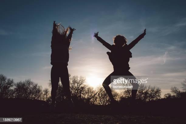 silhouette woman jumping on field against sky during sunset - bortes stockfoto's en -beelden