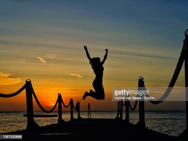 Silhouette Woman Jumping Over Pier At Beach Against Sky During Sunset