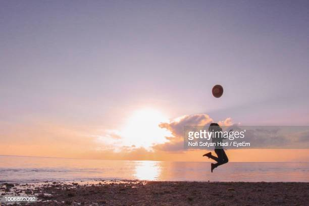 Silhouette Woman Jumping With Hat In Mid-Air At Beach