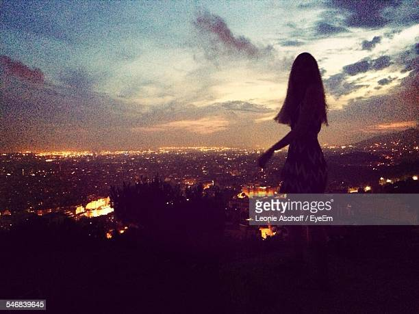 Silhouette Woman Looking At Illuminated Cityscape Against Cloudy Sky At Night