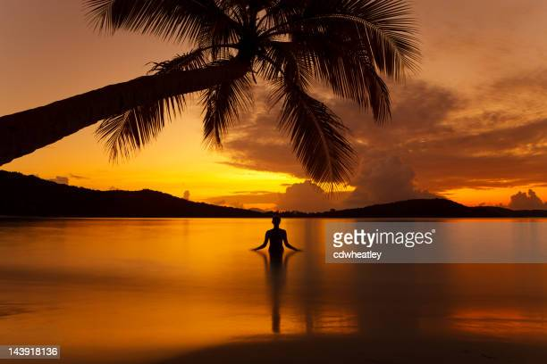 silhouette woman meditating in water during sunset at a beach