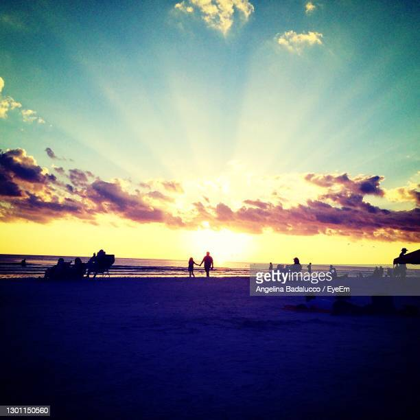 silhouette woman on beach against sky during sunset - siesta key stock pictures, royalty-free photos & images