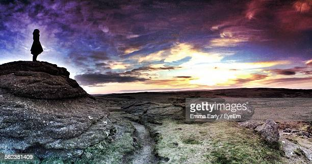 Silhouette Woman On Rocks In Dartmoor National Park Against Sky During Sunset