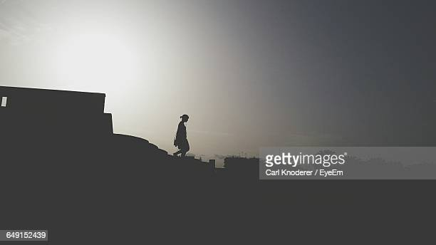 Silhouette Woman On Steps Of Building Against Sky