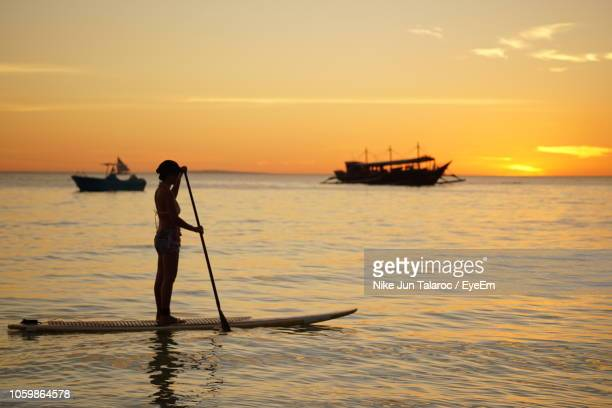 silhouette woman paddleboarding in sea against orange sky - back lit stock pictures, royalty-free photos & images