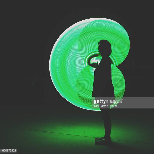 Silhouette Woman Performing Green Light Painting At Night