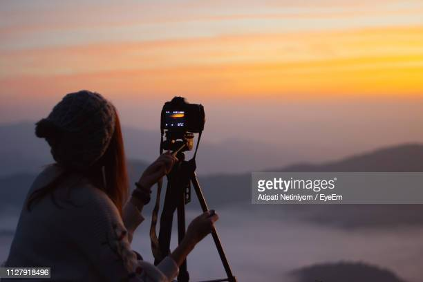 silhouette woman photographing against sky during sunset - digital camera stock pictures, royalty-free photos & images
