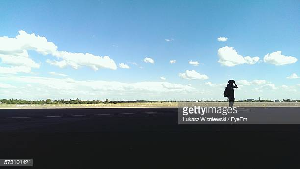 silhouette woman photographing at tempelhof airport against sky - tempelhof airport stock pictures, royalty-free photos & images