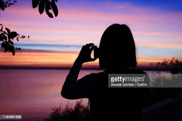 silhouette woman photographing sea with smart phone against sky during sunset - anuwat somhan stock photos and pictures