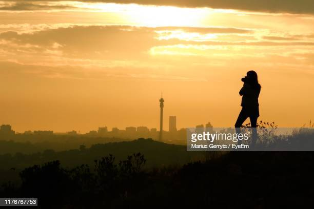 silhouette woman photographing while standing on grass against sky during sunset - johannesburg stockfoto's en -beelden