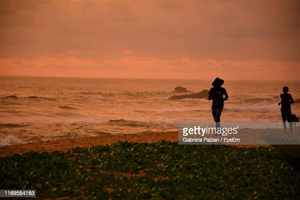 silhouette woman running at beach during sunset - incidental people stock pictures, royalty-free photos & images