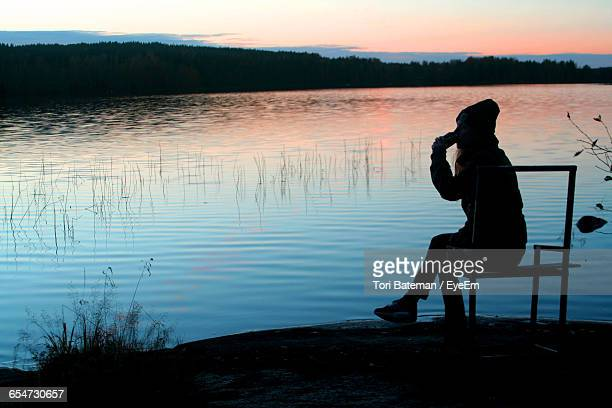 Silhouette Woman Sitting By Lake During Sunset