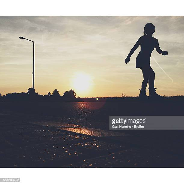 silhouette woman skating on street at sunset - transferbild stock-fotos und bilder
