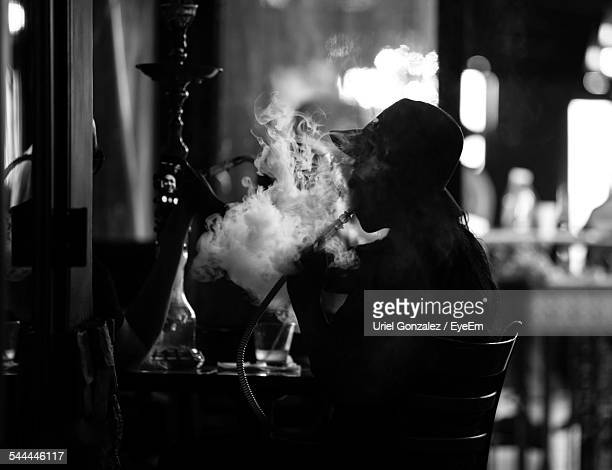 silhouette woman smoking waterpipe in restaurant - chicha photos et images de collection