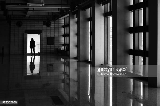 Silhouette woman stand in front of glass door